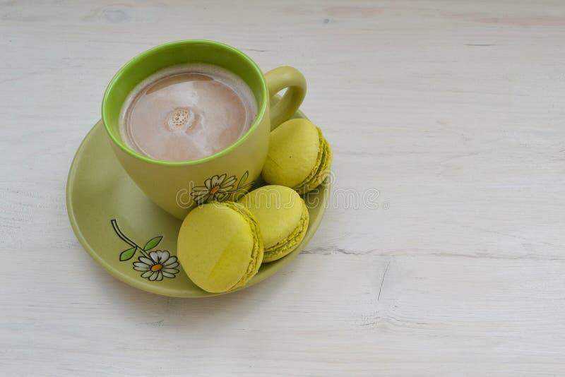 蛋糕macaron或蛋白杏仁饼干和咖啡在破旧的桌上的与拷贝空间 免版税图库摄影