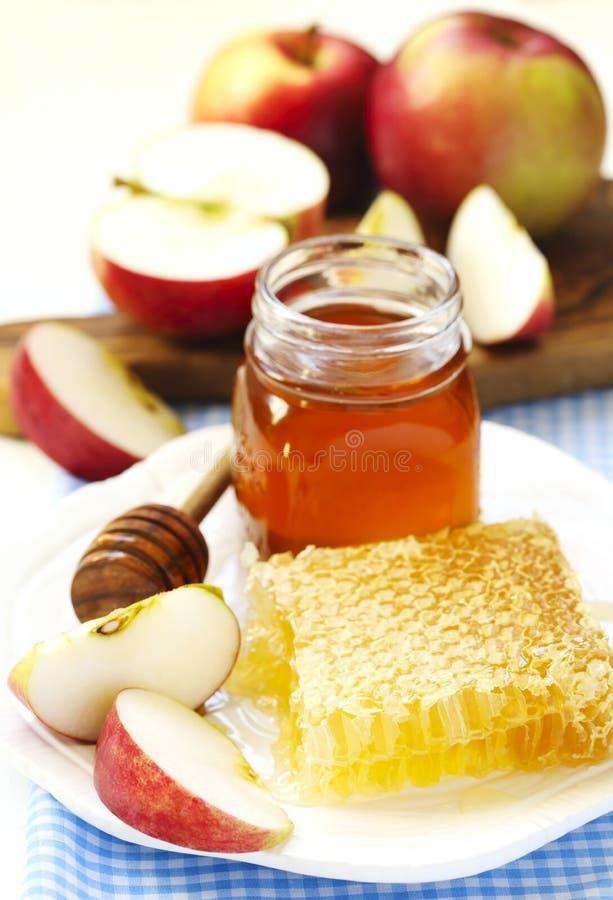 蜂窝用蜂蜜、蜂蜜在玻璃瓶子和切片苹果 免版税库存照片