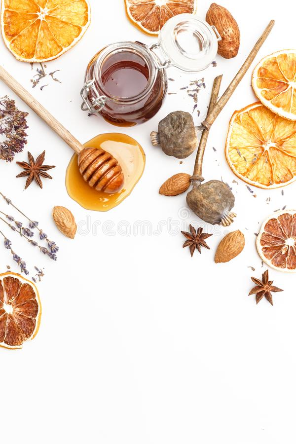 蜂蜜、草本、坚果和香料的木匙子在白色背景 顶视图 图库摄影