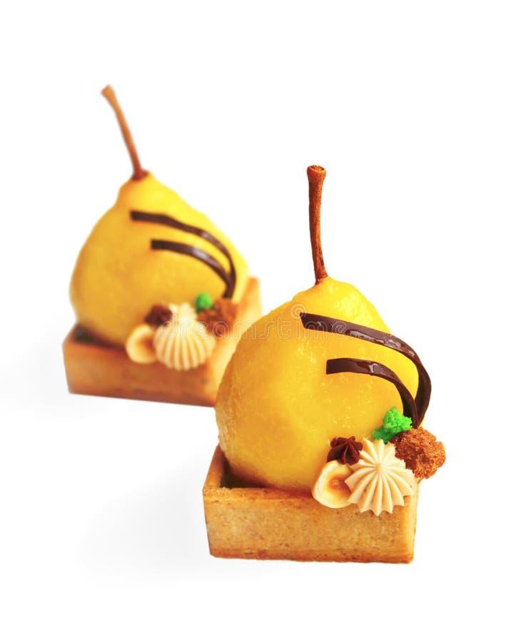 蜂蜜偷猎了与在白色背景和巧克力的梨馅饼隔绝的榛子ganache 库存图片