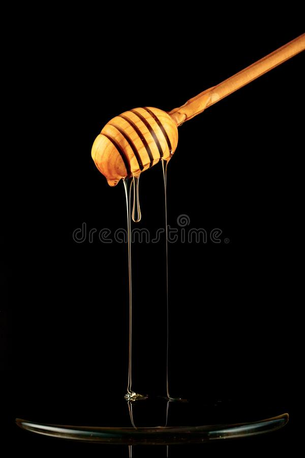 蜂蜜匙子 在黑色背景 滴下的新鲜的蜂蜜 库存照片