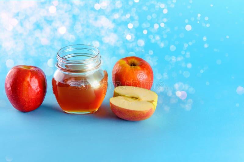 蜂蜜和苹果在蓝色背景 库存照片