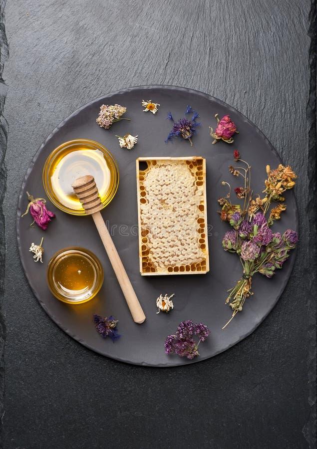蜂蜜梳子和干草本 库存图片