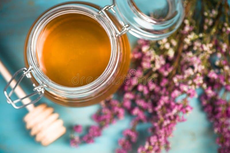 蜂蜜瓶子和紫色秋天石南花花 免版税库存图片