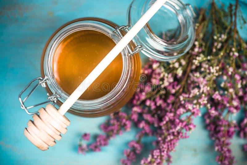蜂蜜瓶子和紫色秋天石南花花 库存照片
