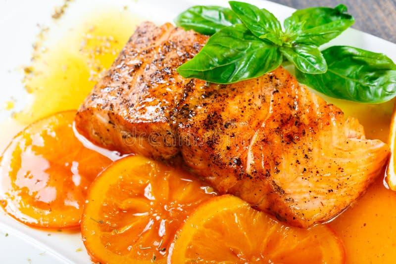 蜂蜜给与橙色切片、香料和basill的内圆角三文鱼上釉在黑暗的背景的白色板材 免版税图库摄影