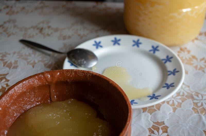 蜂蜜转移从一个更大的容器的到碗里 库存图片