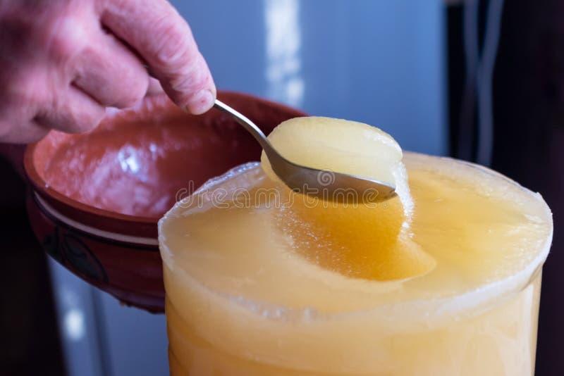 蜂蜜转移从一个更大的容器的到碗里 库存照片