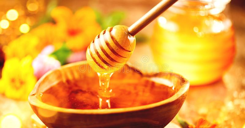 蜂蜜 从蜂蜜浸染工的健康有机厚实的蜂蜜水滴在木碗 点心甜点 免版税库存照片