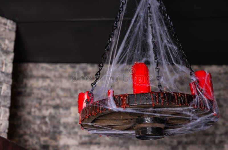 蜘蛛网用红色蜡烛盖了大烛台 免版税图库摄影