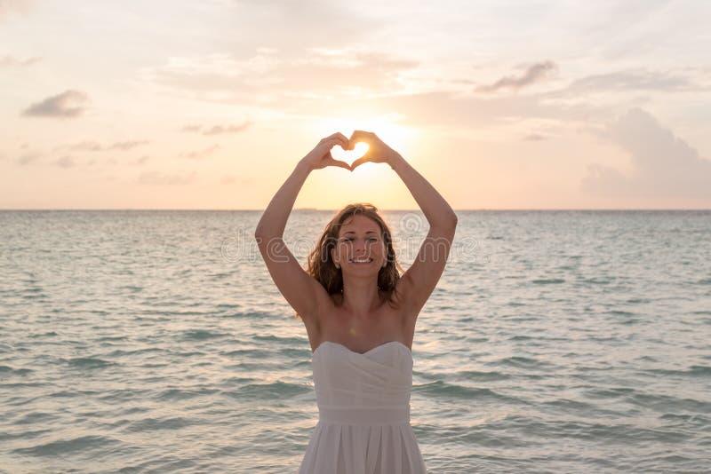 蜜月框架的妇女递入心形,手指心脏框架 看和微笑对在日落期间的照相机 免版税库存照片