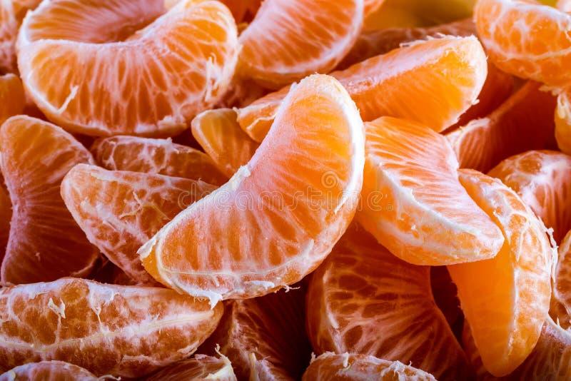 蜜桔或橘子段剥了皮紧密背景纹理 免版税库存图片