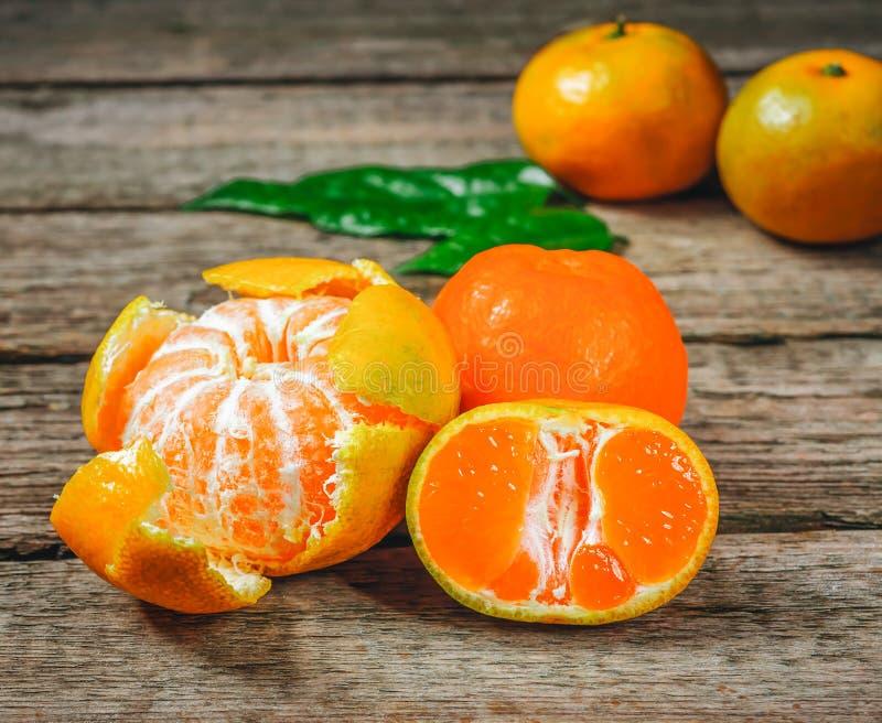 蜜桔普通话,柑桔,与叶子的柑橘水果在与拷贝空间的土气木背景 图库摄影