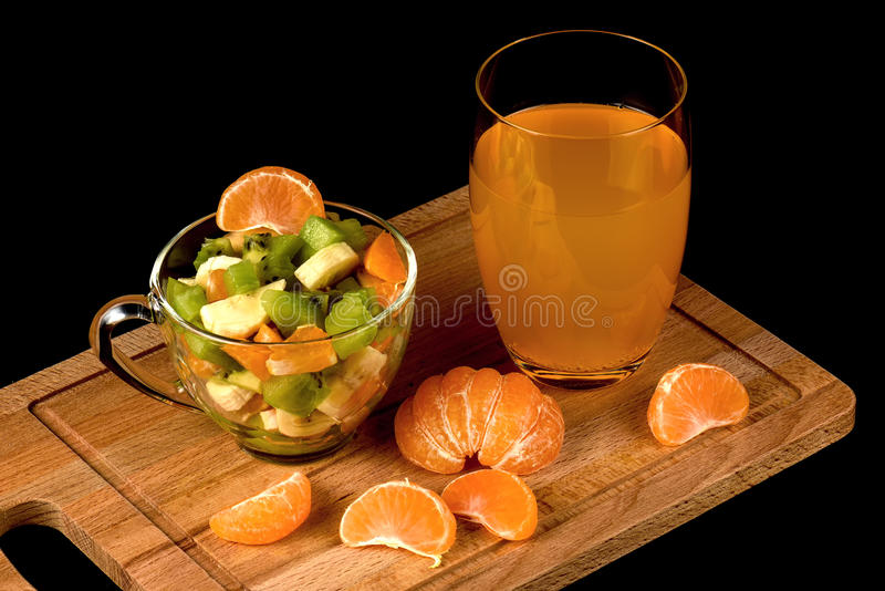 蜜桔的水果沙拉、与饮料的段和玻璃 免版税库存图片