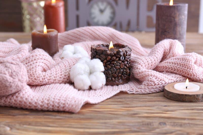 蜡烛、棉花花和温暖的格子花呢披肩在木桌上 免版税库存图片