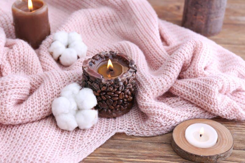 蜡烛、棉花花和温暖的格子花呢披肩在木桌上 库存照片