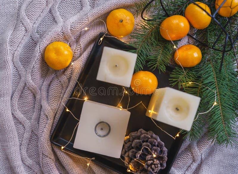 蜡烛、橙色蜜桔、杉木锥体在黑盘子和舒适彩色小灯在knitte格子花呢披肩backgroundand 圣诞节装饰生态学木 免版税库存图片