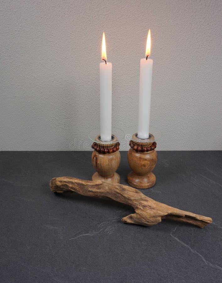 蜡烛与灼烧的蜡烛的光晚餐在灰色木背景的木蜡烛台 库存图片