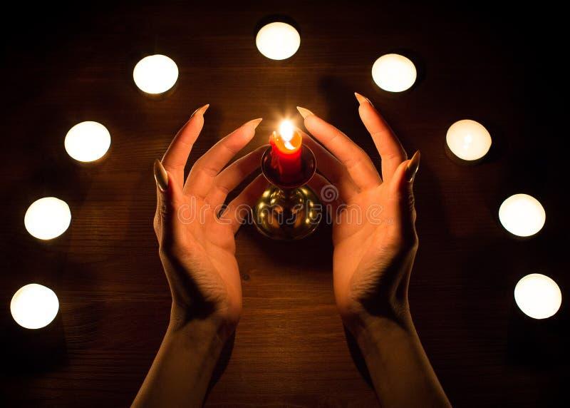 蜡烛和女性手有锋利的钉子的 占卜和巫术,低调 免版税库存照片