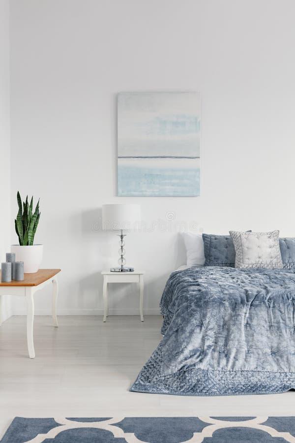 蜡烛和绿色植物白色罐的在桌上在典雅的纽约样式卧室时髦的公寓的,真正的照片 免版税库存照片