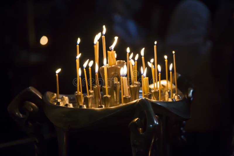 蜡烛在英王乔治一世至三世时期教会里 长的被点燃的蜡烛小组 免版税库存照片
