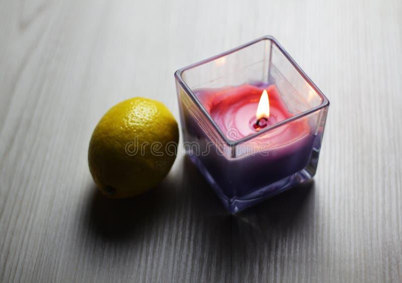 蜡烛用在轻的背景的一个新鲜的柠檬 免版税库存图片