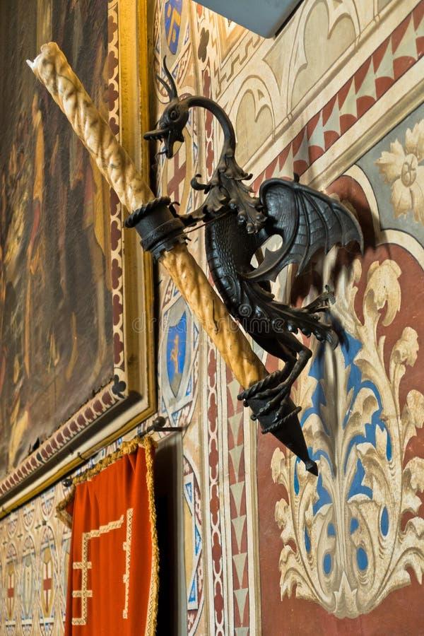 蜡烛立场以一条龙和其他纹章学细节的形式在Priori Pallace里面在沃尔泰拉,最旧的市议会大厅在托斯卡纳 库存图片