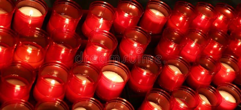 蜡烛许多红色火焰由忠实点燃了在w地方 免版税图库摄影