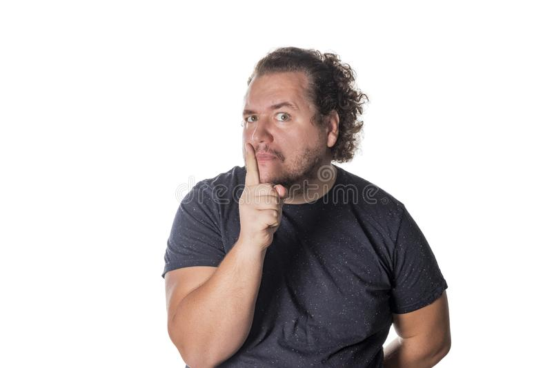 蜷缩帅哥的画象他的与他的手指的嘴 免版税库存照片