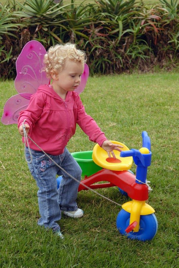 蝴蝶演奏三轮车的女孩litlle 库存图片