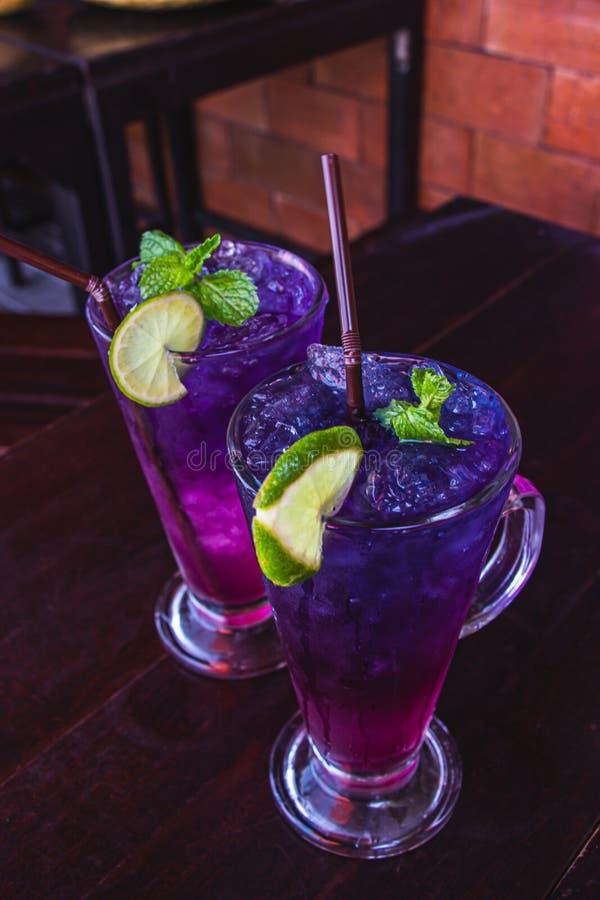 蝴蝶豌豆汁用在黑褐色木桌上把放的清楚的玻璃的柠檬是健康的泰国草本饮料和刷新 ?? 图库摄影
