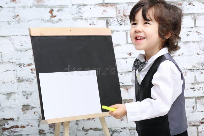 蝶形领结的小微笑的男孩在粉笔板旁边站立 免版税库存照片