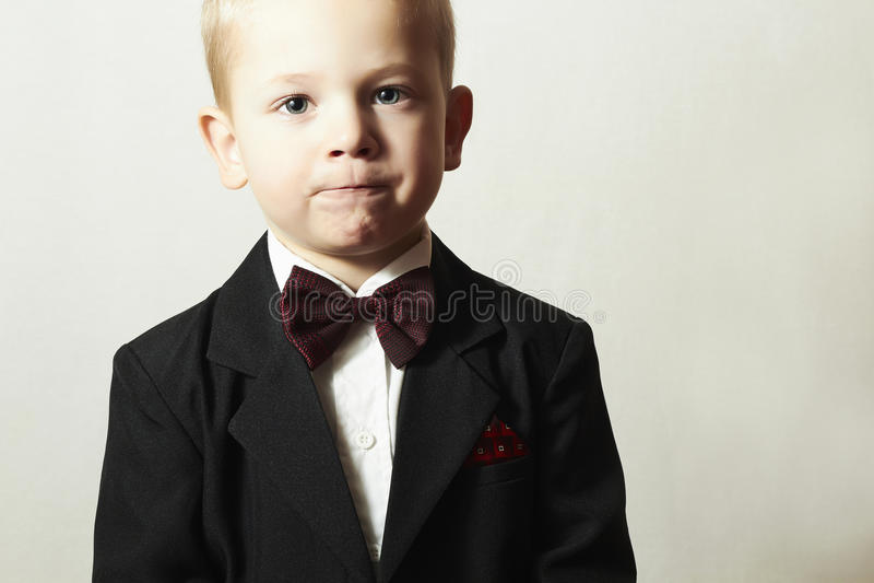 蝶形领结的时兴的小男孩。时髦的孩子。时尚孩子。4岁黑衣服的儿童 图库摄影