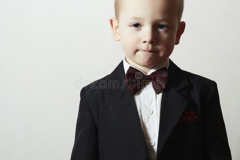 蝶形领结的时兴的小男孩。时髦的孩子。时尚孩子。4岁黑衣服的儿童 免版税库存图片