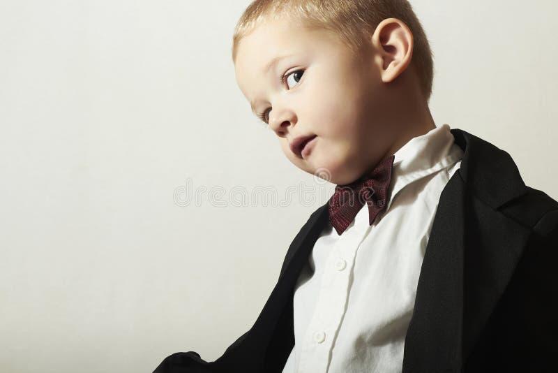 蝶形领结的时兴的小男孩。时髦的孩子。时尚孩子。4岁黑衣服的儿童 库存图片