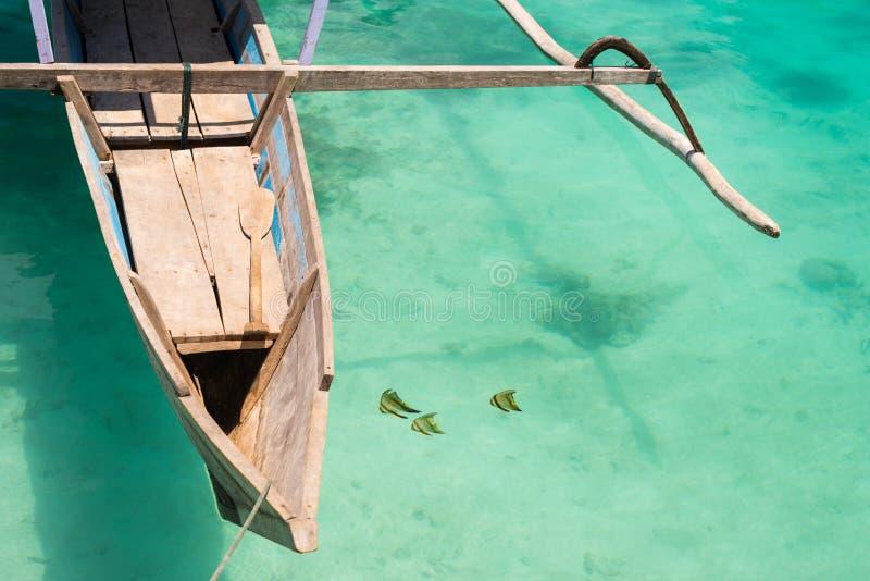 蝴蝶鱼临近传统小船 库存照片
