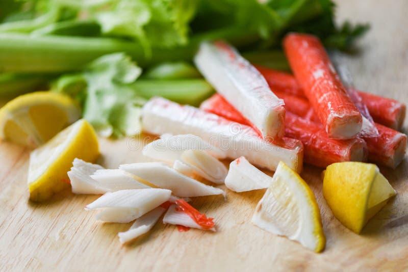螃蟹棍子用柠檬和新鲜的芹菜菜在木板材 库存图片
