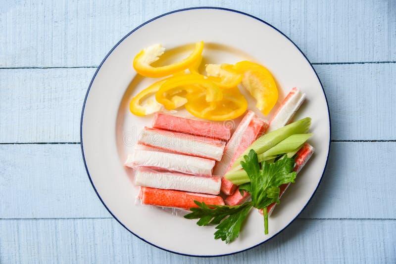 螃蟹棍子用甜椒胡椒和新鲜的芹菜菜在板材食物 免版税库存照片