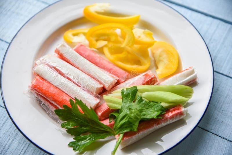 螃蟹棍子用甜椒胡椒和新鲜的芹菜菜在板材 库存图片
