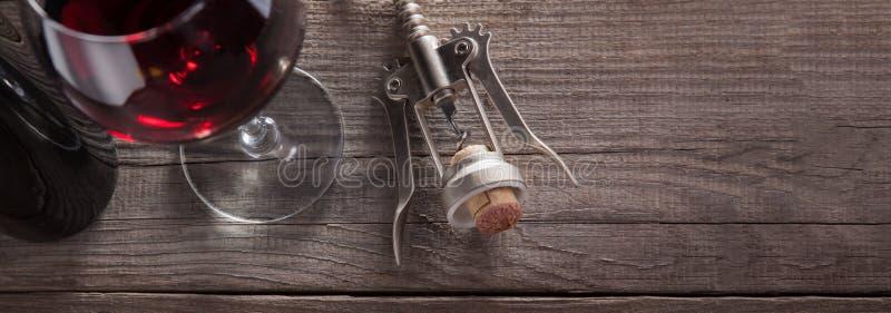螺旋式前进和一杯在一张老木桌上的酒 免版税库存图片