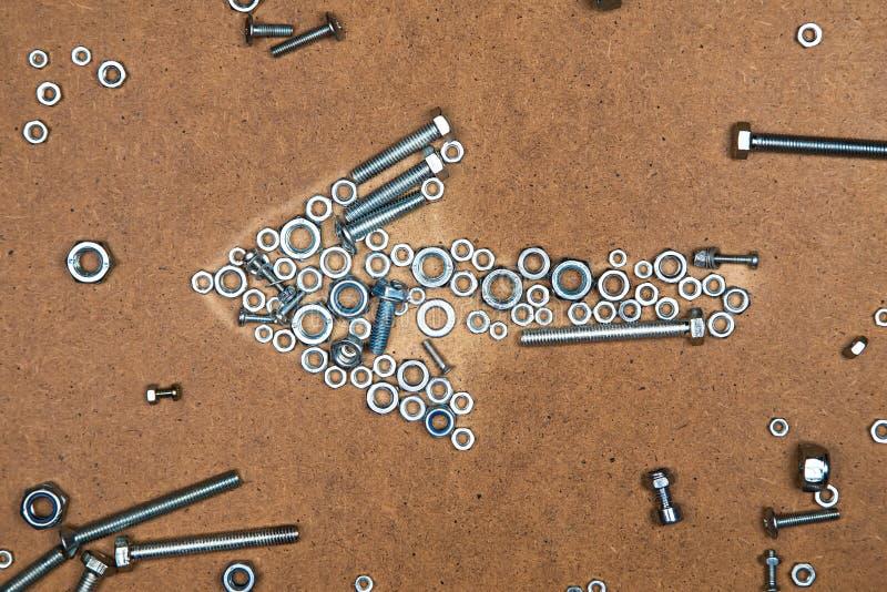 从螺栓和坚果的明亮的左箭 免版税库存图片