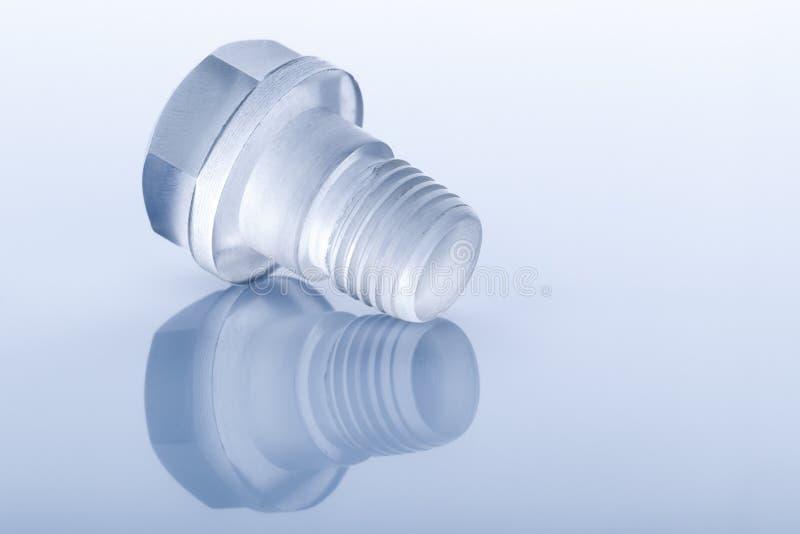 螺栓由透明塑料制成在蓝色 库存图片