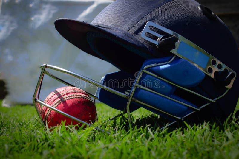 蟋蟀halmet和球在一个绿色草甸 免版税图库摄影