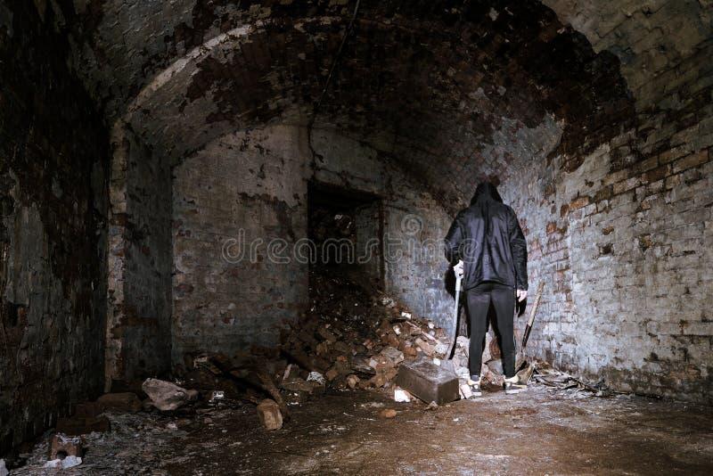 蠕动的人在有铁锹的遗弃砖室站立 库存图片