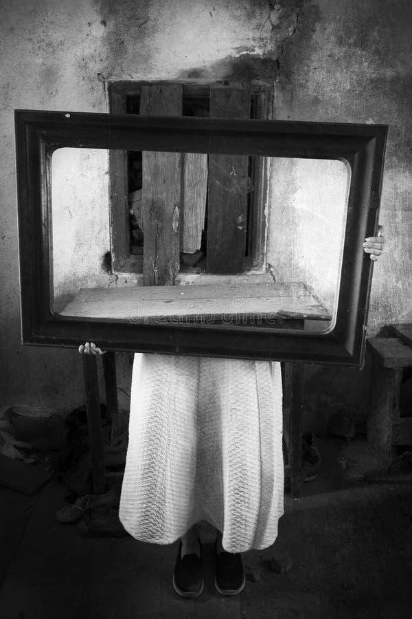 蠕动的老内部举行的镜子的恐怖女孩 免版税库存图片