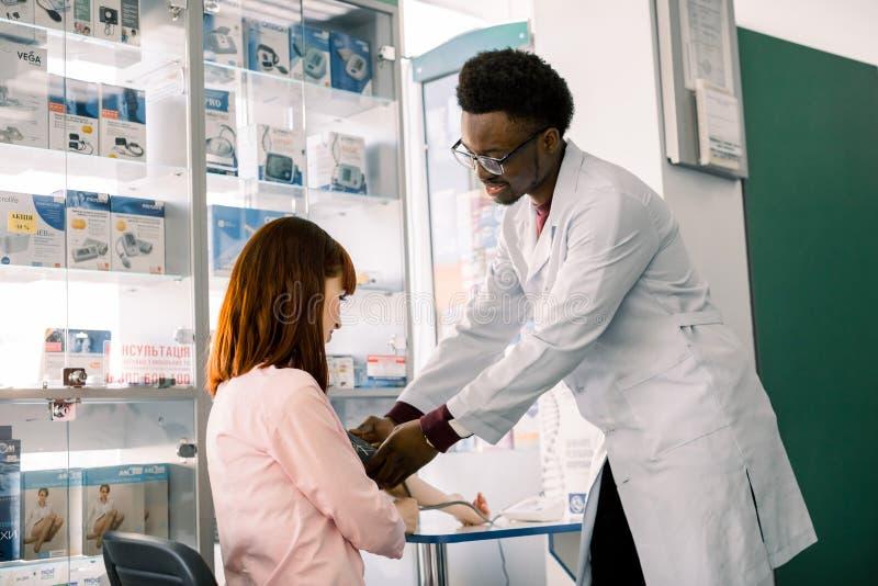 血压测量 非洲人药剂师或医生和年轻女人患者 现代药房背景 ?? 图库摄影