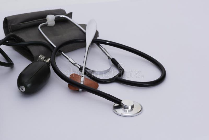 血压计袖口、反射锤子和听诊器在白色ba 免版税库存照片