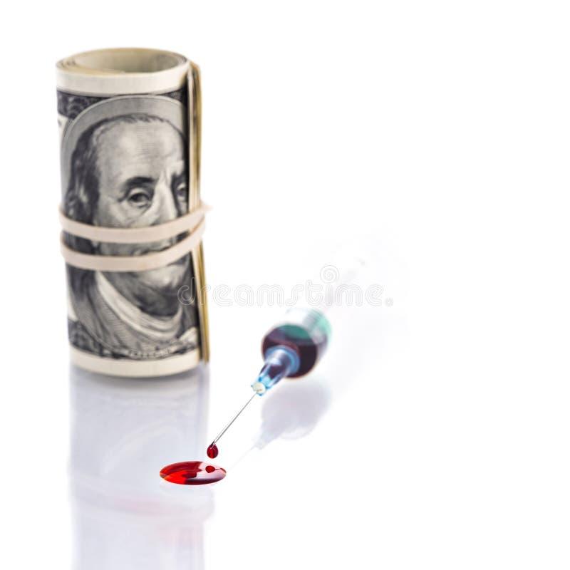 血液从与100美元的注射器针下降钞票rollo 免版税图库摄影