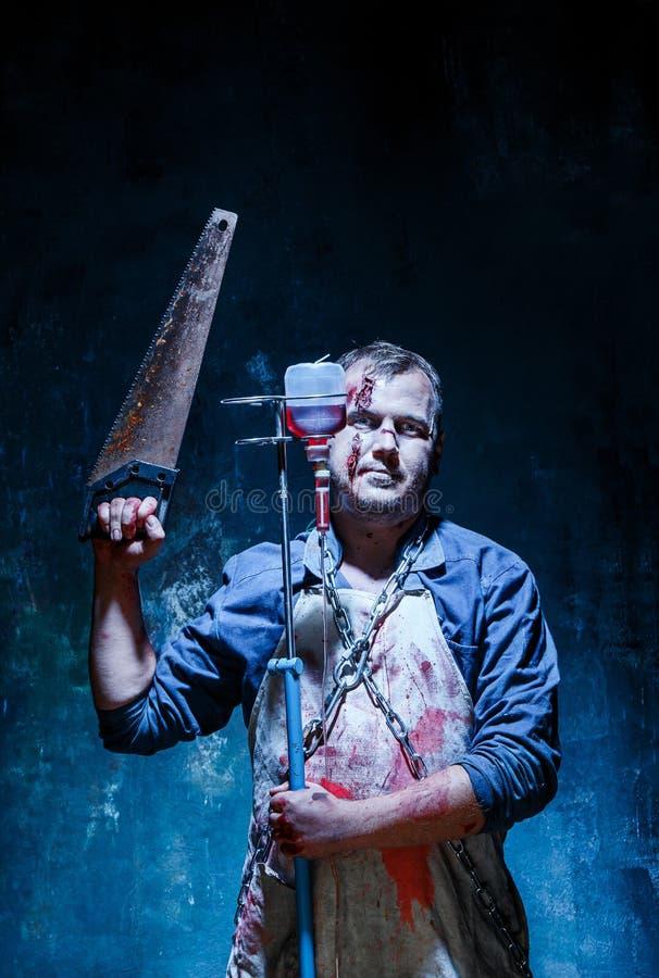 血淋淋的万圣夜题材:作为屠户的疯狂的凶手与看见了 免版税图库摄影