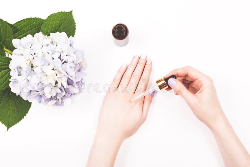 血清瓶或精油在妇女手上 免版税图库摄影